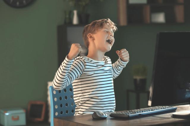 Boy celebrating a coding win at his computer