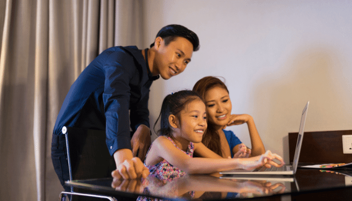 Family smiling as daughter codes at her computer