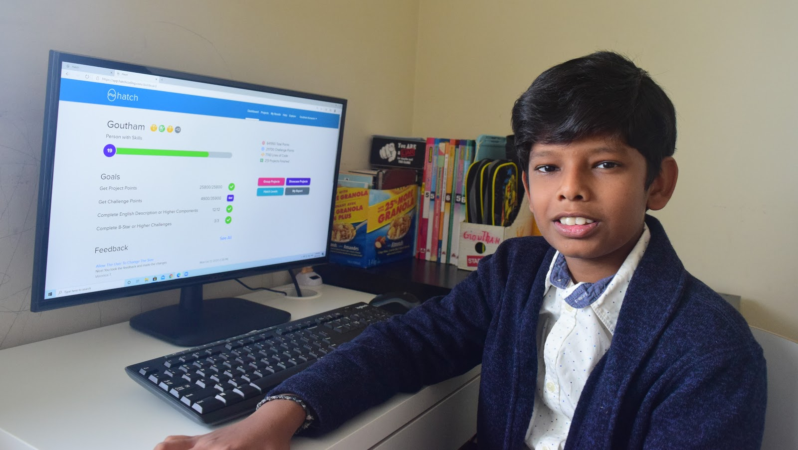 Boy smiling at his computer while working on Hatch Coding's platform