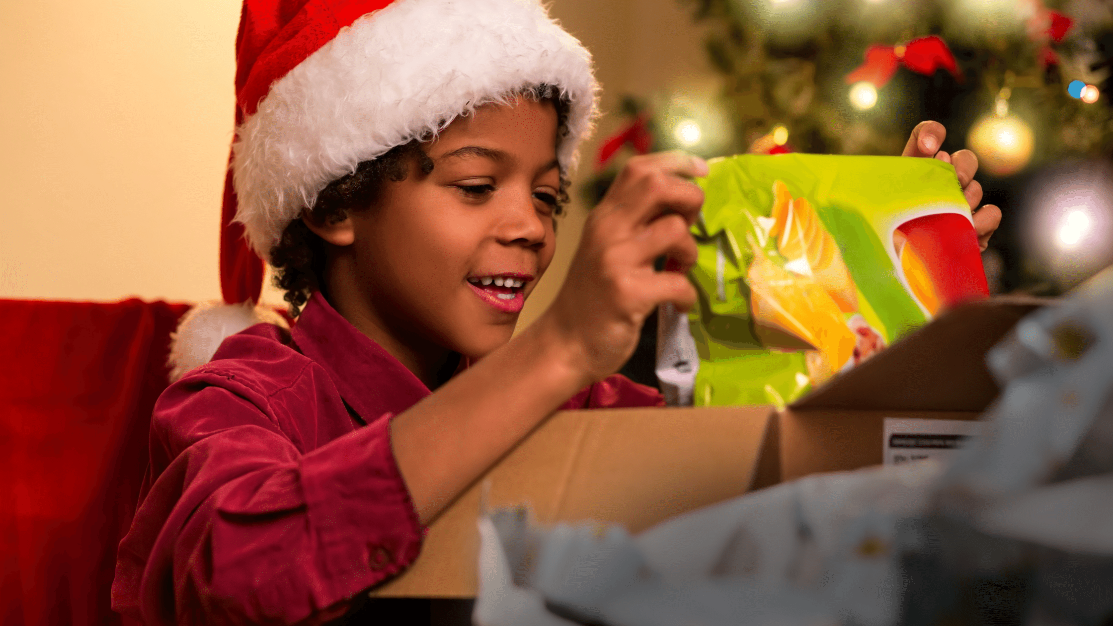 Boy smiling while opening a holiday gift of a coding program
